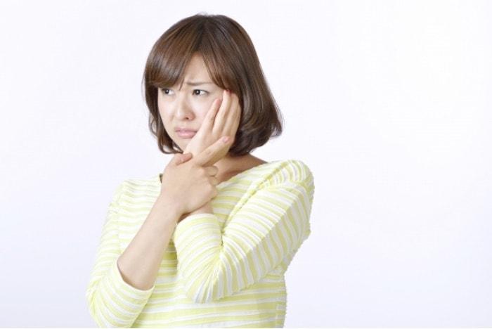 痛くて歯を抑えている女性