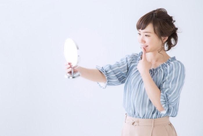 歯を鏡で確認している女性