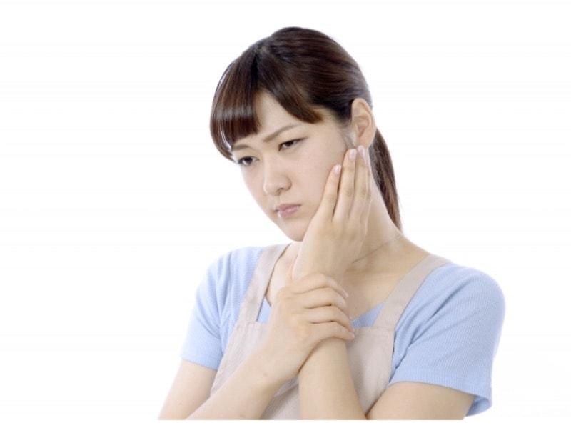痛みがあり頬を抑えている女性